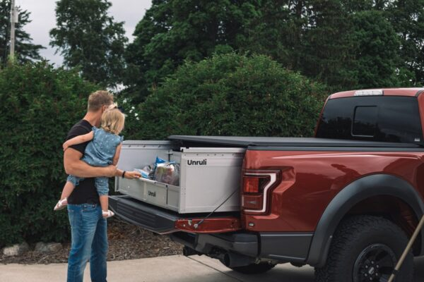 father and daughter removing groceries from tool box in back of pickup truck