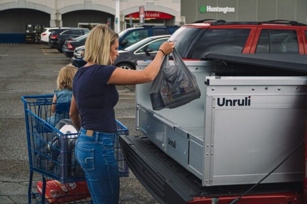 woman and baby loading groceries in back of pickup truck